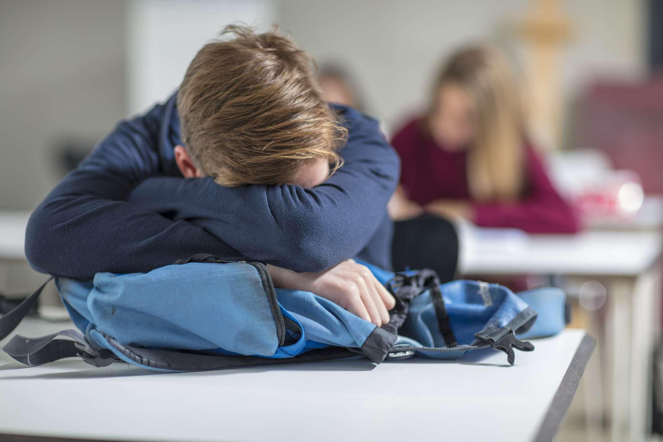 teenage boy sleeping on desk in class