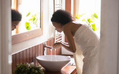 African American woman wash face in modern bathroom - stock photo