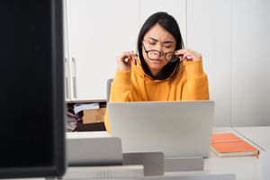 Young woman in front of a computer holding and removing her glasses.