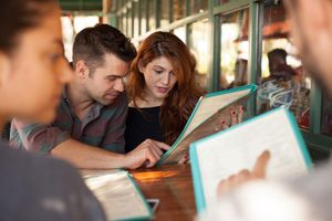 Four friends looking at menus in a restaurant