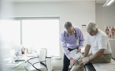 A doctor examining his patient's mans knee in an examination room