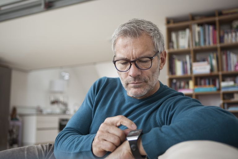 Man at home sitting on couch looking at watch