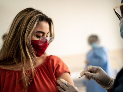 A young Hispanic woman with glasses and a red face mask getting a shot.