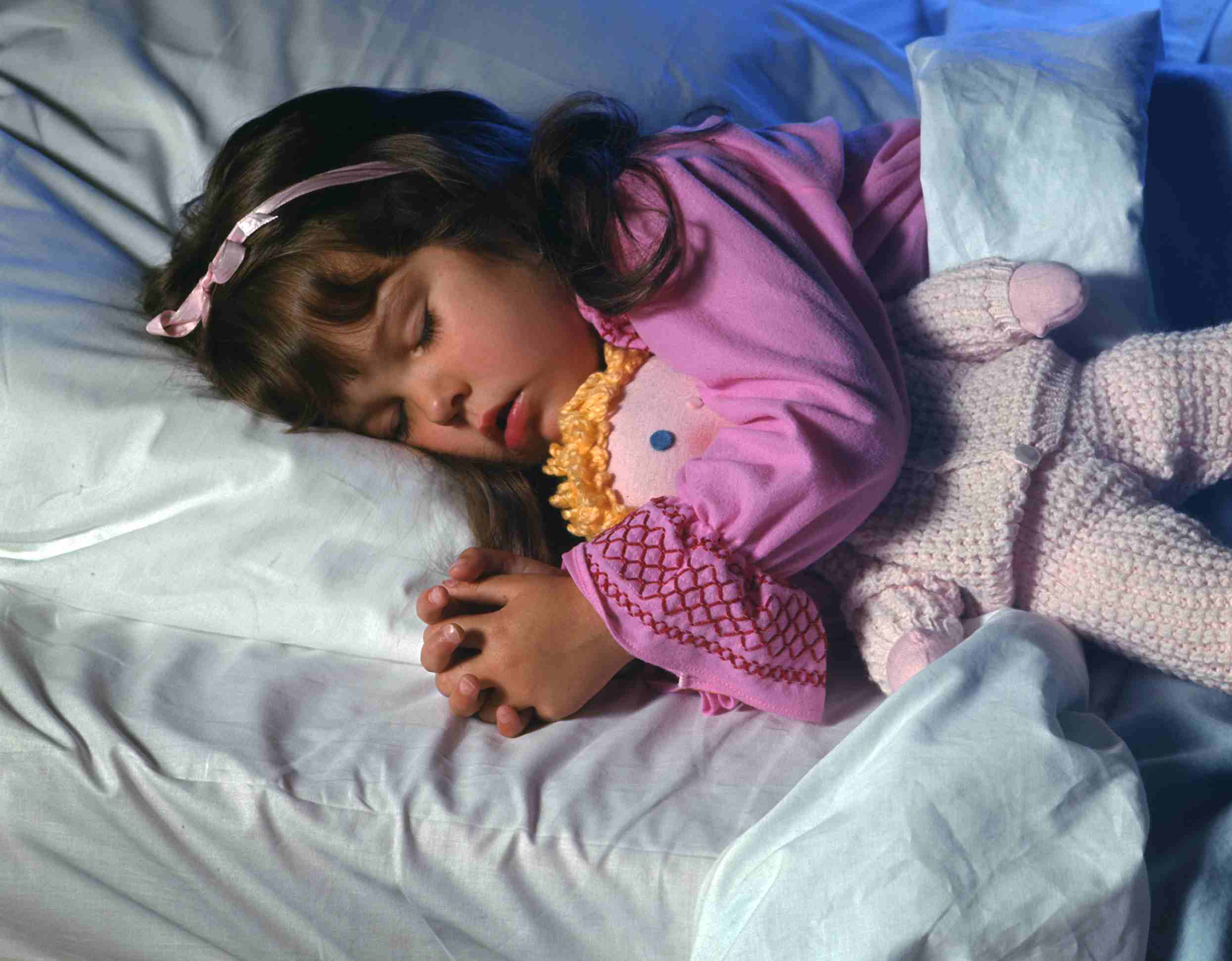Young girl sleeping in bed with her doll