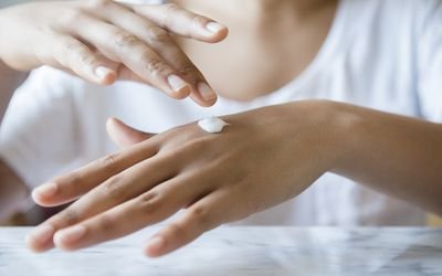 African American woman applying lotion to hand