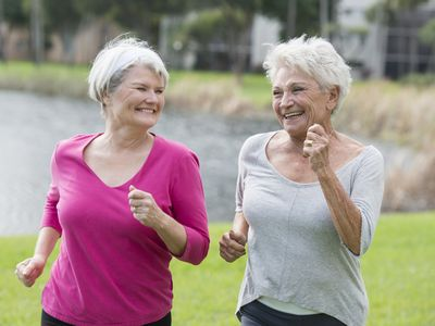 Two happy women walking together outside