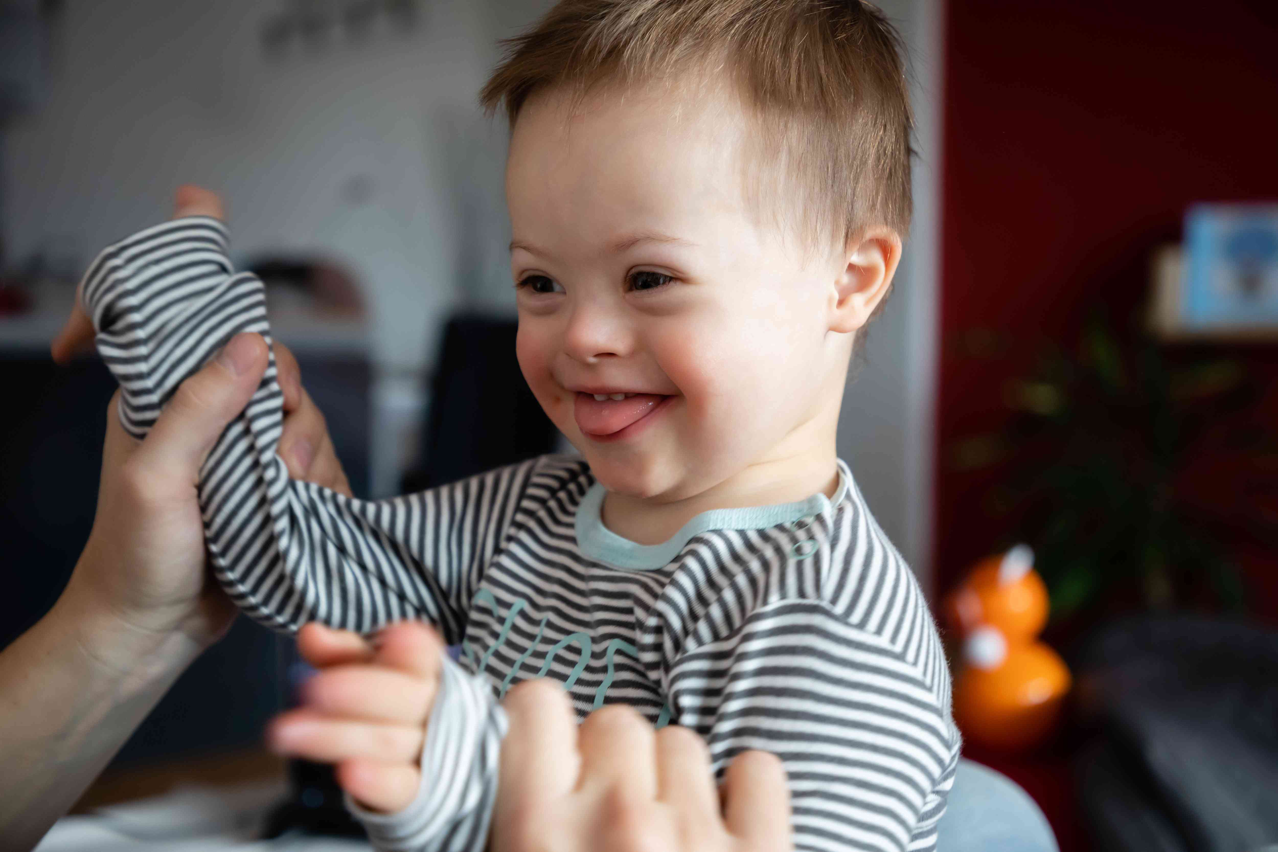 Cute boy with Down syndrome playing with dad on in home