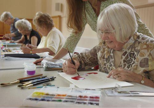 Senior woman painting in an art class