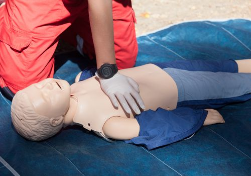 Rescuer performing child CPR with one hand on a practice dummy
