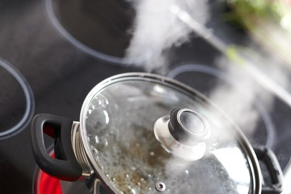 Pot of boiling water on stove steaming