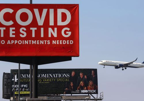 Delta plane flying near a COVID-19 testing sign