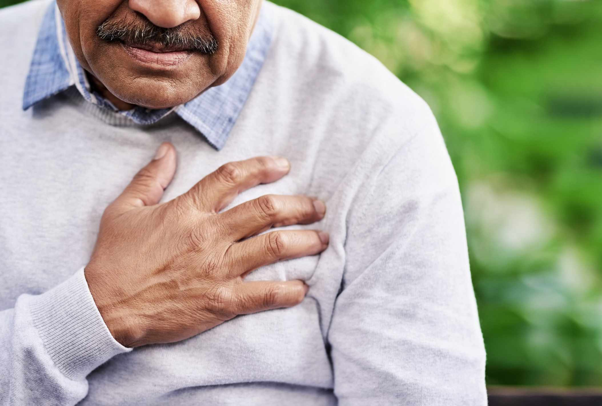 A man clutching his chest in pain