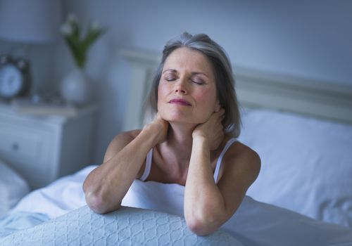 Woman sitting up in bed massaging her own neck