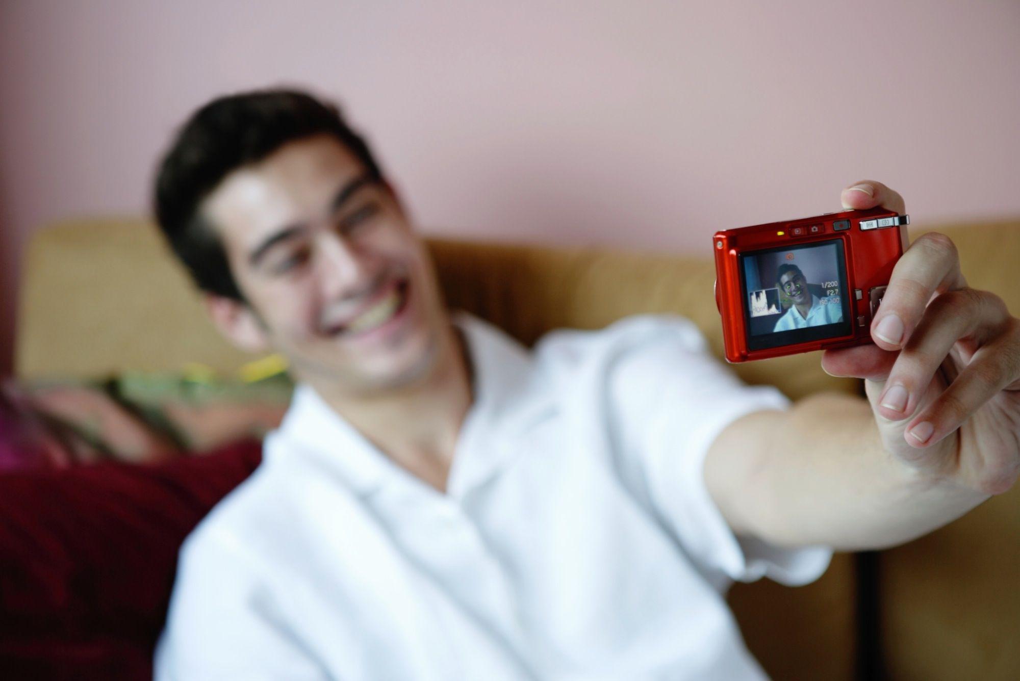 Man holding camera, taking photograph of himself