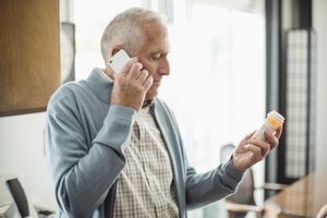 Older man on the phone with pills