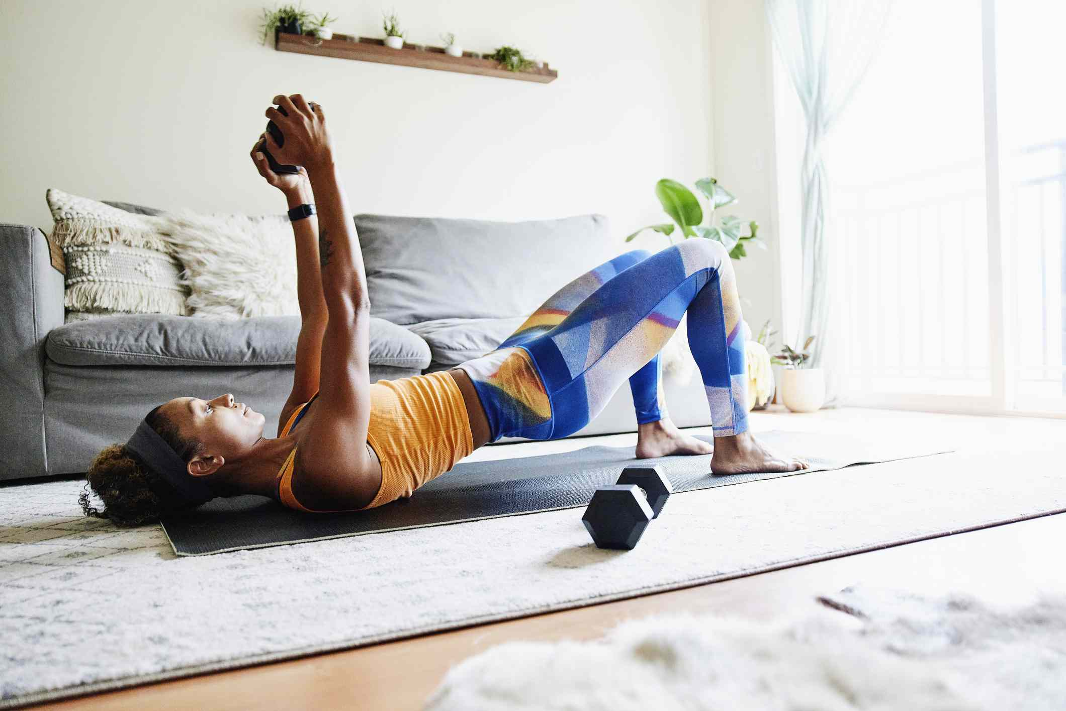 Woman working out with weights while exercising in home