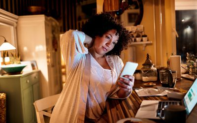 Close up of a mature woman using her phone at home at night