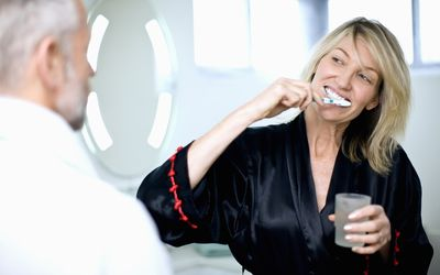 Woman brushing her teeth while holding glass of water