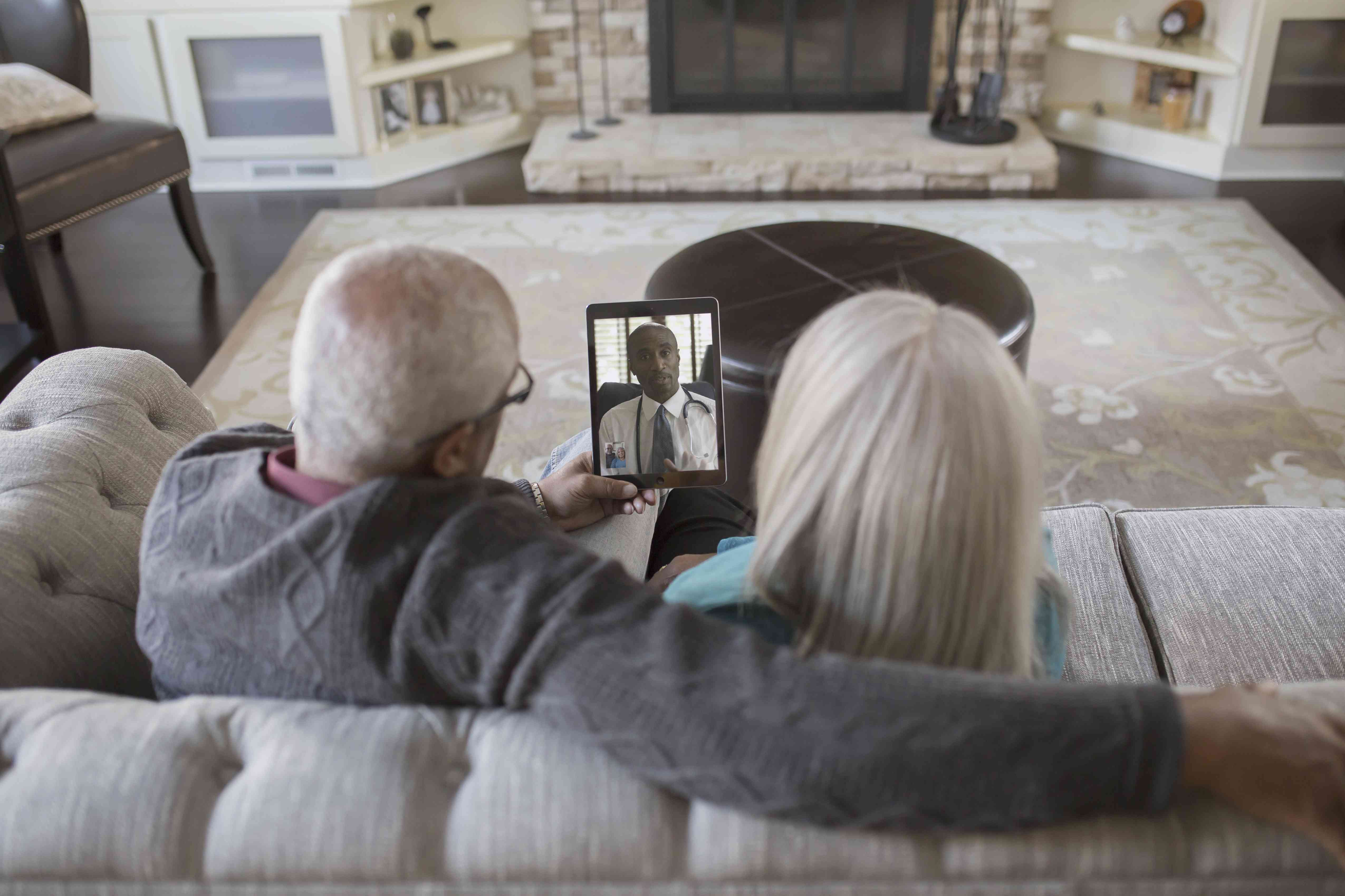 An older couple video chatting with their doctor