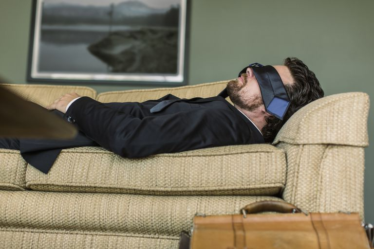 Man laying on couch with tie over his eyes