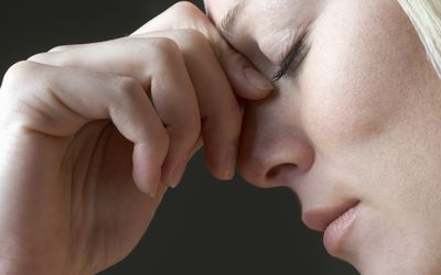 A woman squeezing the bridge of her nose