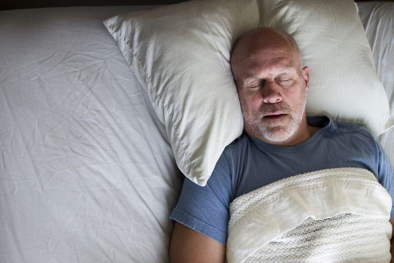 senior man snoring in bed