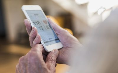 Close up of an older adult's hands holding a smartphone with medical information on screen.