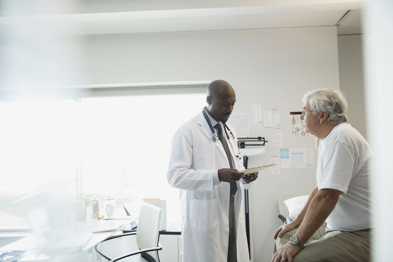a doctor reviewing medical chart with senior man