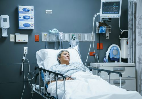 Mixed race patient sleeping in hospital bed