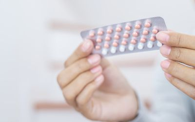 Woman hands opening birth control pills in hand. Eating Contraceptive Pill.