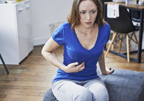 Woman experiencing heartburn