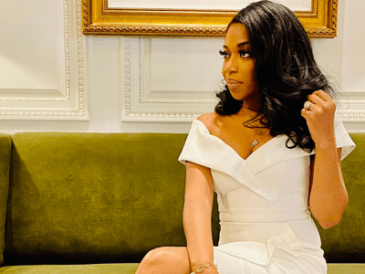 Tanika Gray Valbrun sitting on couch in white dress