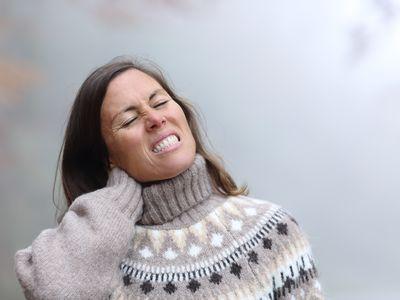 woman suffering neck ache in winter