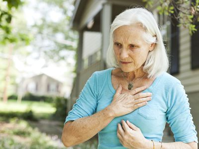 a senior woman holding her chest