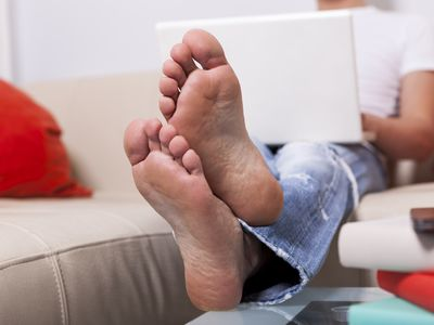 Man sitting barefoot on a couch using laptop at home