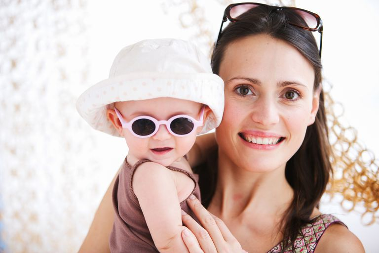 Mother holds baby wearing sunglasses and a sun hat