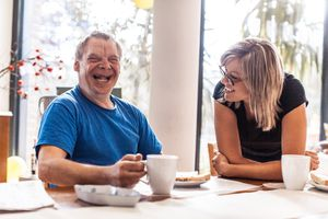 Adult Man Portrait with a Down Syndrome holding a coffee cup