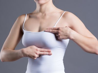 Breast test, woman examining her breasts for cancer, heart attack, pain in human body