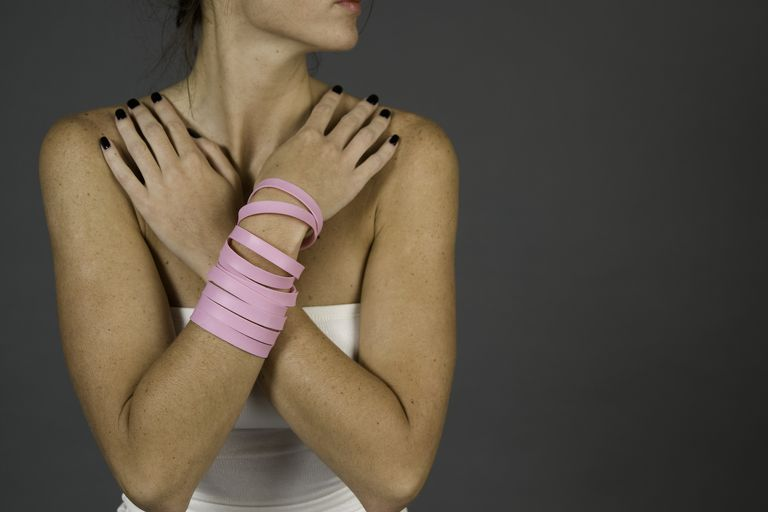 woman with pink breast cancer bracelets holding her arms crossed over her chest