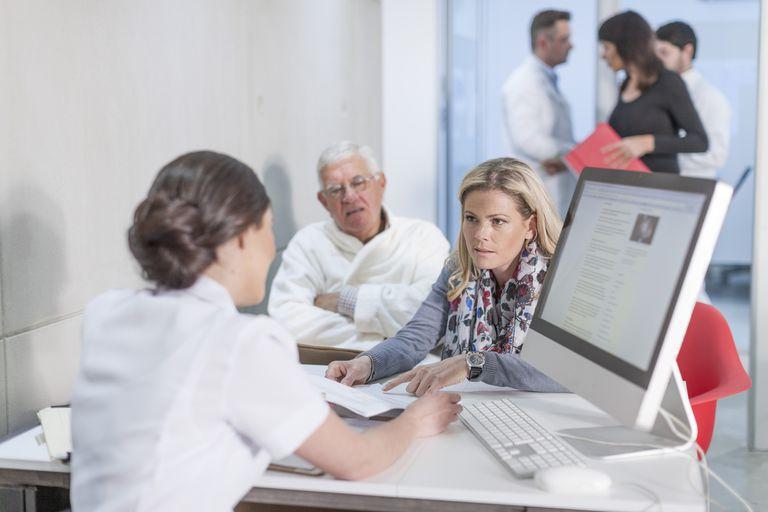 Nurse helping patients at clinic reception
