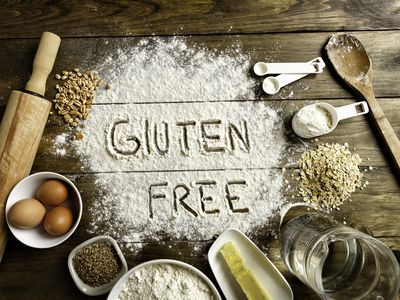 Gluten free bread ingredients and utensils on wood frame background