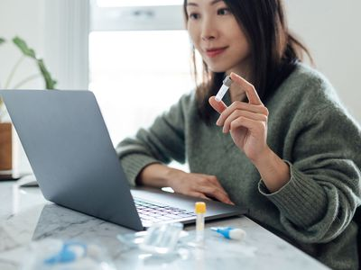 Woman using blood test kit at home while doing health check and consultation online