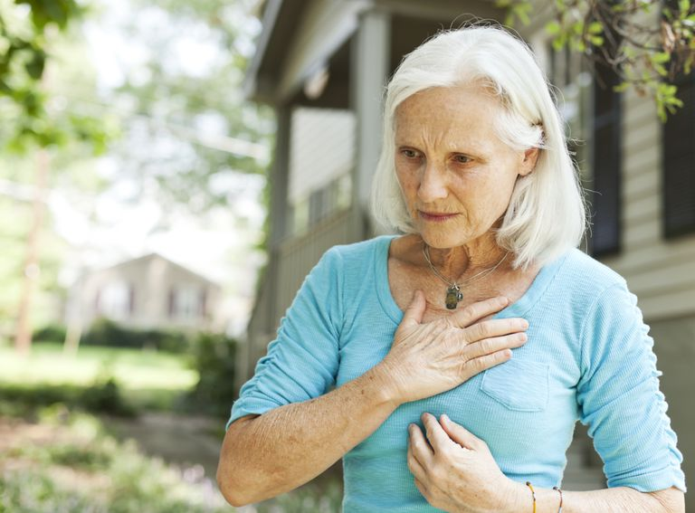 Woman holding chest in pain