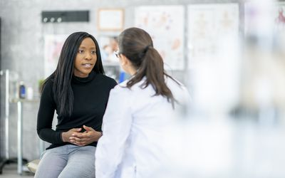 A woman and her doctor discuss abdominal symptoms