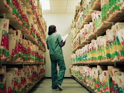Nurse searching shelves full of medical records