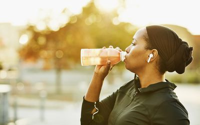 Muslim woman drinking sports drink after working out in park on fall afternoon