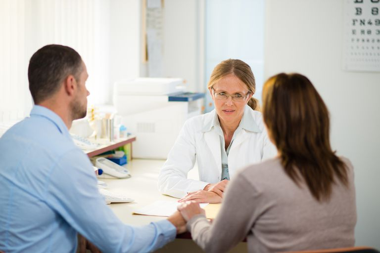 female doctor talking to couple
