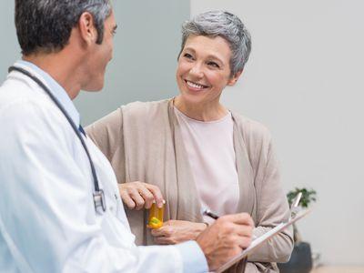 Senior doctor in conversation with senior woman holding medicine box.