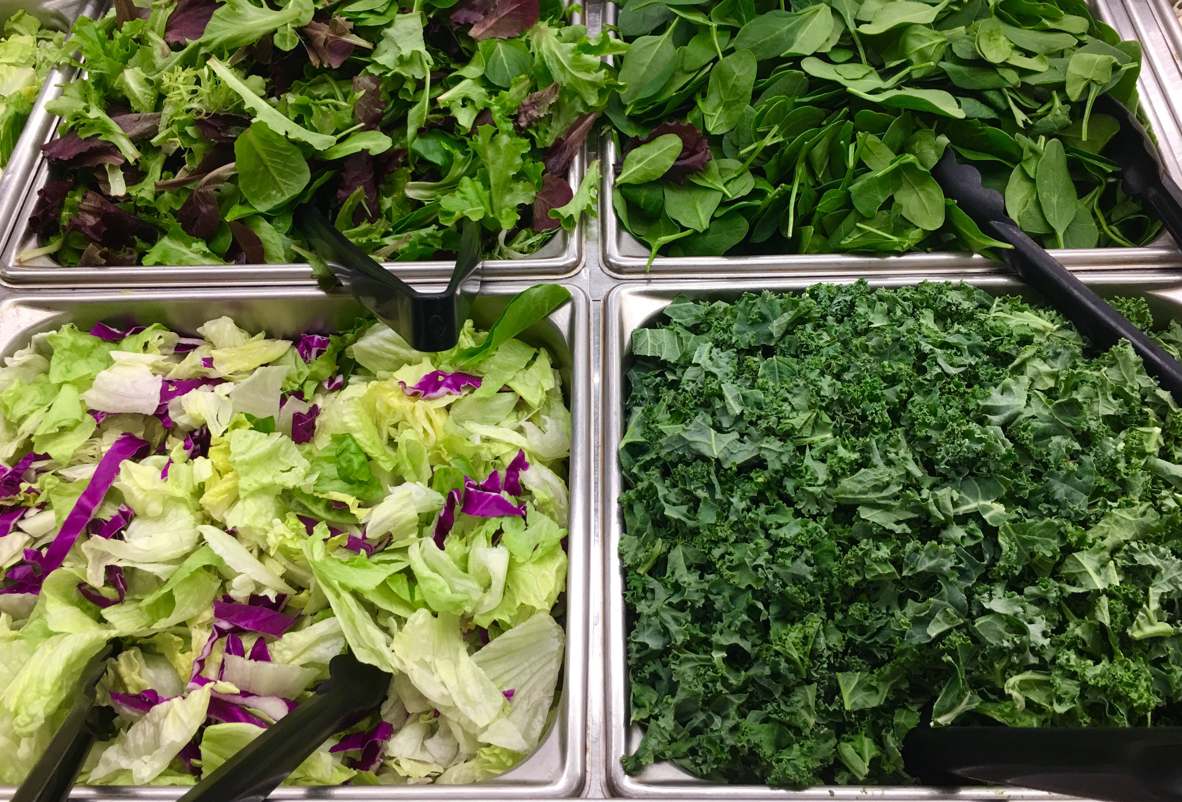 different salad greens in a salad bar