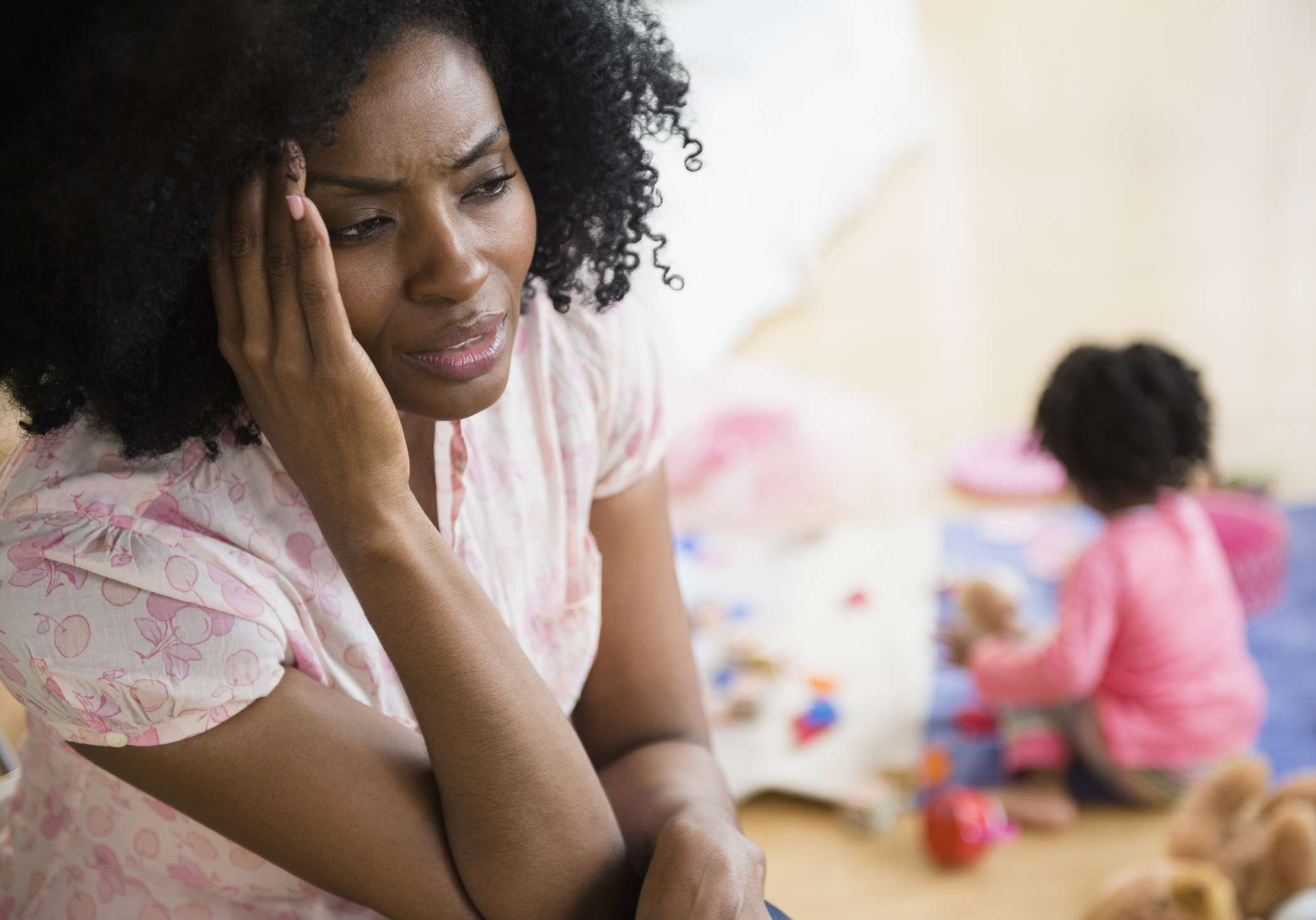 Black woman holding head with stress